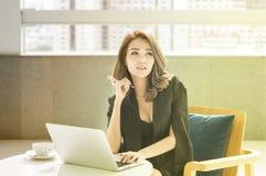 年轻美丽的iAsian女实业家与计算机一起使用在公司中认为成功 库存图片