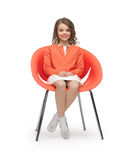 便衣的青春期前的女孩坐椅子 库存照片