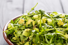 美丽的Paleo蔬菜沙拉用黄瓜和鲕梨在深灰木背景,水平 库存照片