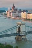 美丽的Szechenyi铁锁式桥梁在布达佩斯匈牙利和议会 免版税库存照片