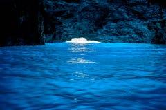 美丽相互蓝色洞通过微小的入口在背景中访问了在卡斯特龙岛希腊海岛上  免版税库存图片