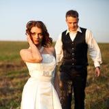 美丽立场-新娘摆在,当新郎走到她在t时 免版税库存图片