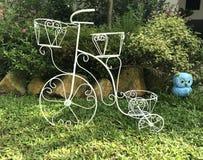 美丽装饰在庭院背景的弯曲的钢自行车 免版税库存图片