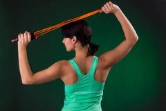 美丽运动,健身妇女身分,摆在与在灰色背景的一条跳绳与绿色背后照明 免版税库存照片