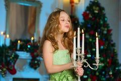 美丽迷住相当一棵新年树的背景的白肤金发的儿童女孩 库存照片