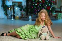 美丽迷住相当一棵新年树的背景的白肤金发的儿童女孩 免版税图库摄影