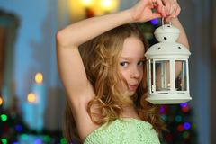 美丽迷住相当一棵新年树的背景的白肤金发的儿童女孩 免版税库存图片