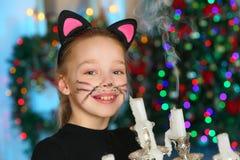 美丽迷住相当一棵新年树的背景的白肤金发的儿童女孩 图库摄影