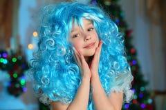 美丽迷住相当一棵新年树的背景的白肤金发的儿童女孩 库存图片