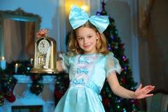 美丽迷住相当一棵新年树的背景的白肤金发的儿童女孩 免版税库存照片