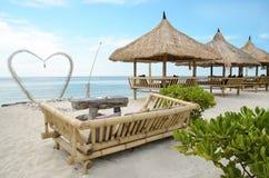 美丽送Gili Travangan海岛背景的和两把椅子海滩有海洋的在伞,印度尼西亚下 免版税库存照片
