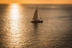 美丽风景和热带 游艇或风船在海日落与阳光反射在水 免版税库存照片