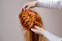 美丽,与长期,红发长毛的女孩,美发师编织一条辫子,在美容院的特写镜头 免版税库存图片