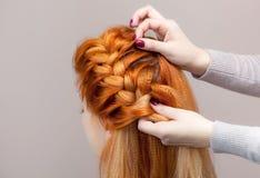 美丽,与长期,红发长毛的女孩,美发师编织一条辫子,特写镜头 免版税库存照片