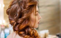 美丽,与长期,红发长毛的女孩,美发师编织法国辫子,在美容院 免版税库存图片