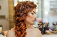美丽,与长期,红发长毛的女孩,美发师编织法国辫子,在美容院 免版税库存照片