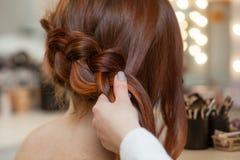 美丽,与长期,红发长毛的女孩,美发师编织法国辫子,在美容院的特写镜头 库存照片