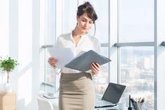 美丽,严肃的顾问佩带的玻璃和一套正式办公室衣服,拿着她的工作固定式,看照相机 免版税库存照片