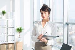 美丽,严肃的顾问佩带的玻璃和一套正式办公室衣服,拿着她的工作固定式,看照相机 库存照片