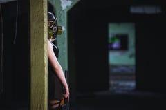 美丽,女孩岗位启示女孩立场在有防毒面具和机枪的被放弃的工厂 库存图片