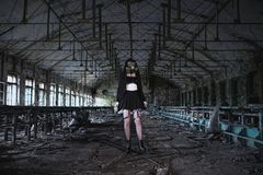 美丽,女孩岗位启示女孩立场在有防毒面具的被放弃的工厂 免版税库存照片
