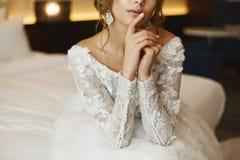 美丽,性感和时兴的棕色毛发的少妇,鞋带礼服的,摆在内部-新娘` s早晨 库存照片