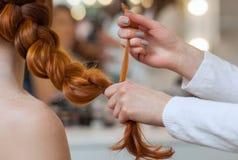美丽,红色长毛的女孩,美发师编织法国辫子,在美容院的特写镜头 库存图片