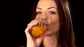 美丽,运动的妇女饮用的汁液,在黑色 影视素材