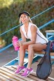 美丽,适合的女孩与瓶水坐体育场背景 羽毛球球员概念 库存照片