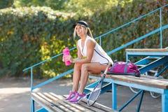 美丽,适合的女孩与瓶水坐体育场背景 羽毛球球员概念 图库摄影