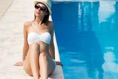 美丽,年轻,性感的女孩在夏天享用在水池附近 免版税库存图片