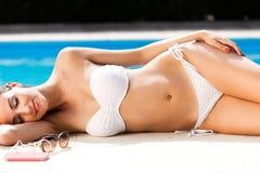 美丽,年轻,性感的女孩在夏天享用在水池附近 免版税库存照片