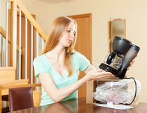 美丽年轻白肤金发与新的咖啡机器在家 免版税库存照片