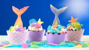美人鱼与五颜六色的闪烁尾巴、壳和海生物的题材杯形蛋糕 库存照片