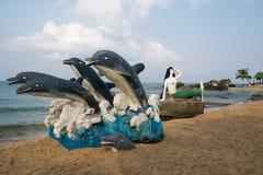 美人鱼和海豚的雕塑在海滩 免版税库存照片