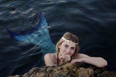 美人鱼在偷看在岩石外面的水中游泳 库存照片