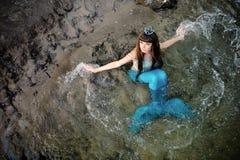 美人鱼在岸的水中 免版税库存照片