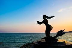 美人鱼雕象和孩子剪影  免版税库存图片