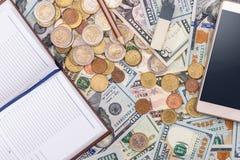 美元、欧洲硬币、电话计算器笔记薄笔和铅笔 免版税图库摄影