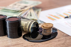 美元与溢出的油的钞票在书桌上 有石油生产日程表的计算器 免版税库存图片