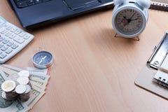 美元与白色闹钟,指南针,计算器的钞票,白色 免版税库存图片