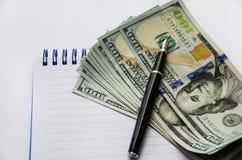 美元和一支笔在一个白色笔记本 免版税库存图片