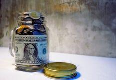 美元和硬币用货币装载一个玻璃技巧瓶子 看dow 免版税图库摄影