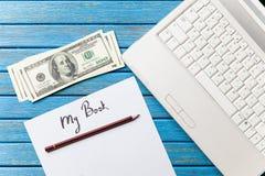 美元和纸与我的书题字在笔记本附近 免版税库存照片