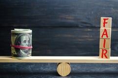美元和题字`公平的`在木块 平衡 公平价值定价,金钱债务 公平交易 合理的价格 Justifi 库存照片