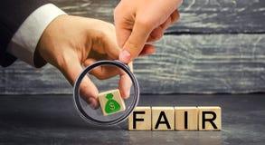 美元和题字`公平的`在木块 平衡 公平价值定价,金钱债务 公平交易 合理的价格 Justifi 免版税库存照片