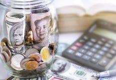 美元在一个玻璃瓶子o的票据对中国元票据和硬币 库存照片