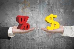美元标志和百分率符号用两只手 免版税库存照片