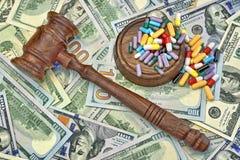 美元现金背景的法官惊堂木和药物 免版税库存图片
