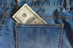 100美元笔记细节在蓝色牛仔裤的口袋的 库存照片